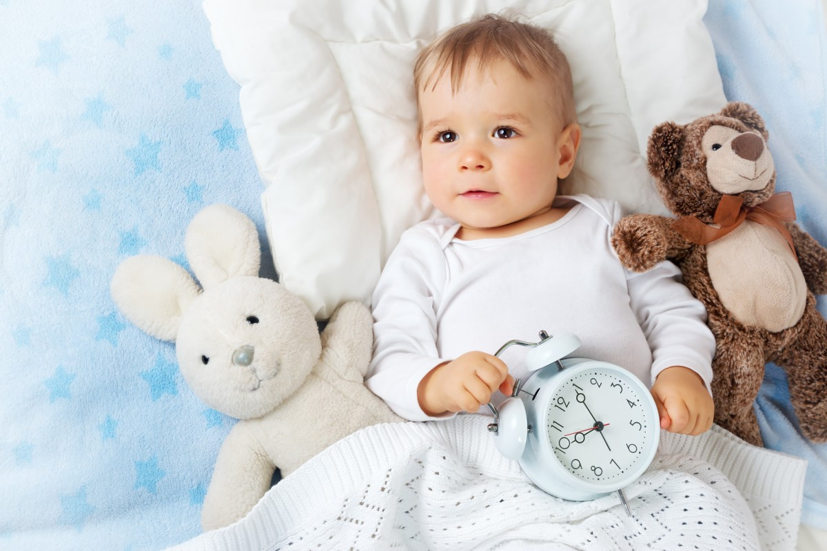 baby holding clock to illustrate the concept of parenting time as viewed by a Clinton Township family lawyer