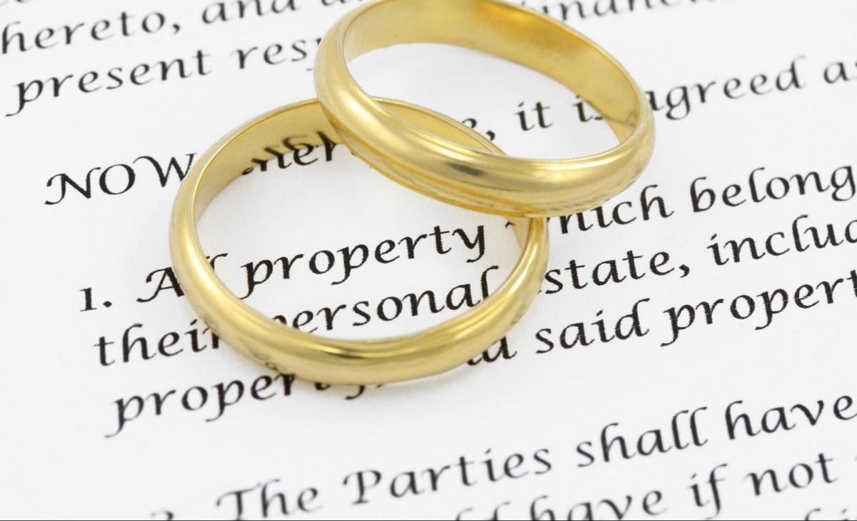 wedding rings on a prenuptial agreement document on the desk of a Clinton Township divorce attorney