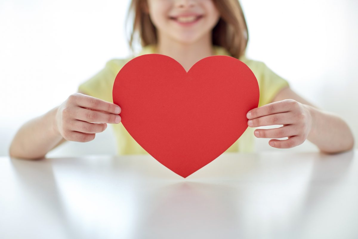 child holding paper heart from the perspective of a Clinton Township child support lawyer