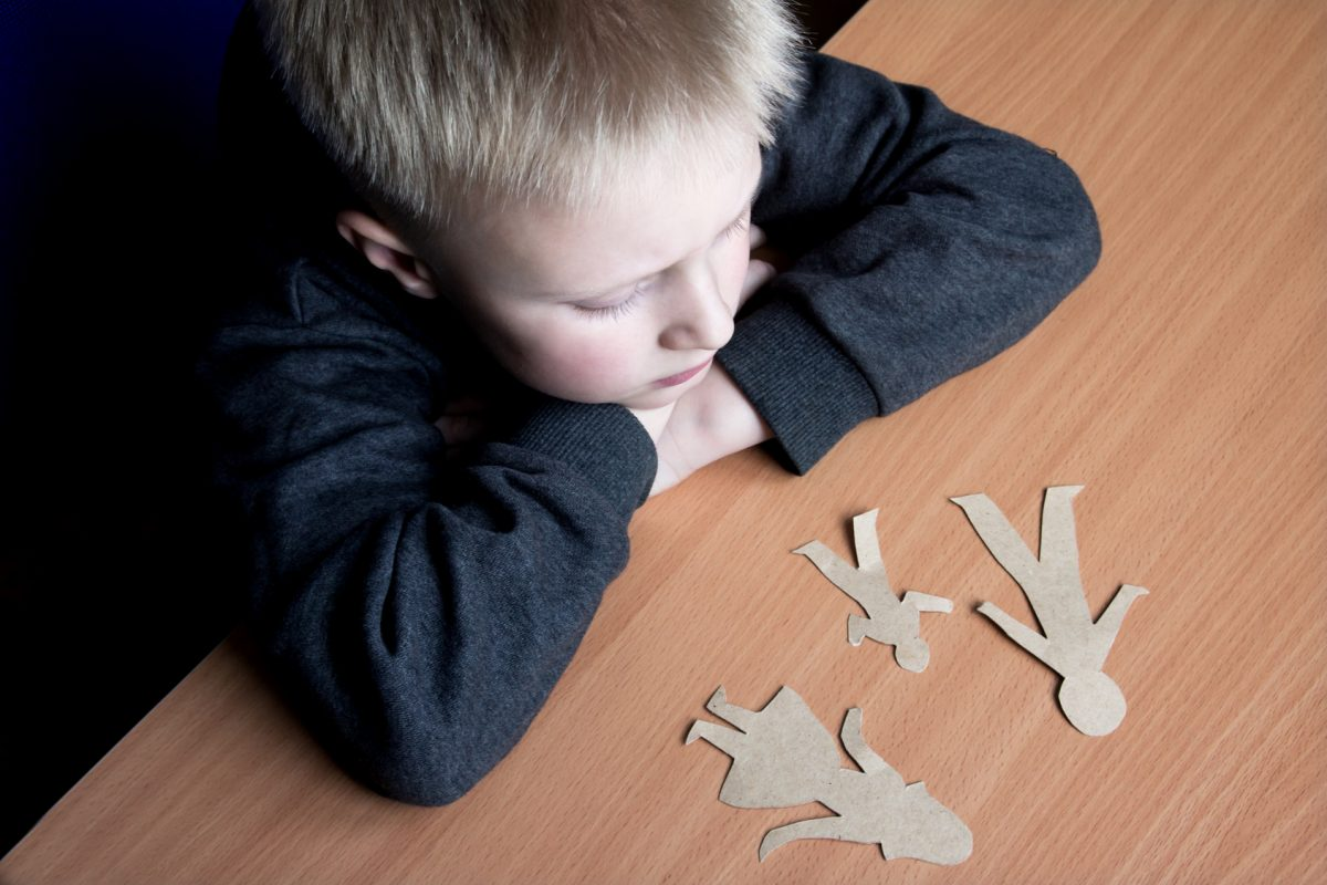 child looking at paper dolls from the perspective of a Clinton Township child custody attorney