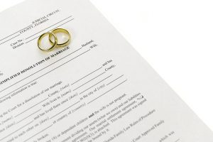 Divorce Form With Pair Of Wedding Rings representing the work a clinton township divorce lawyer does.