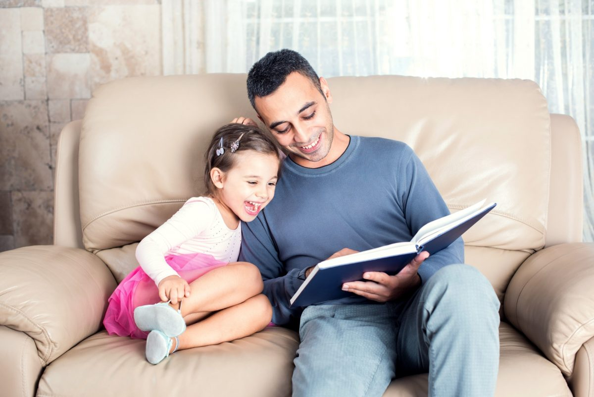Little girl and father are enjoying reading book together and if you need a parenting time attorney find one in Warren.