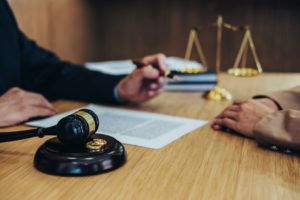 Divorce concept with gavel and wedding rings representing how our family law attorneys can assist you with divorce