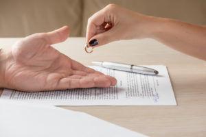 Wife and husband signing divorce papers representing how our Clinton Township divorce attorneys can help you with your case