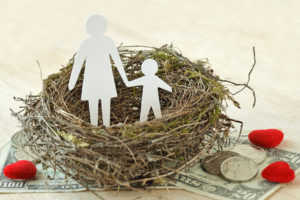 Paper mother and son in a nest surrounded by hearts and money representing how our Troy attorneys can assist you with child custody