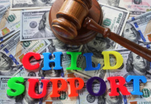 Child support spelled out with gavel and money representing how our Shelby Township child support lawyers can answer your questions