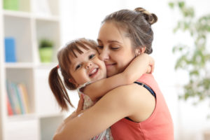 Mom hugging child in pigtails