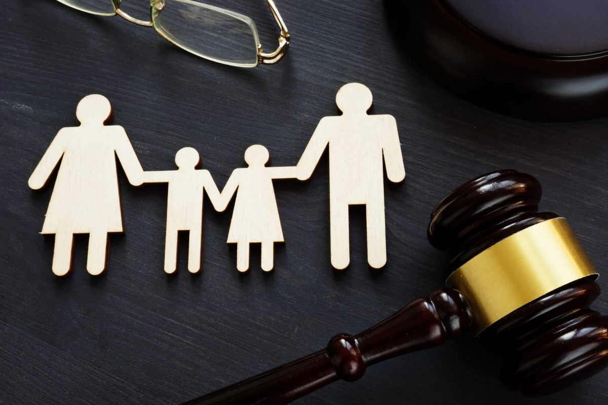 Paper family holding hands with judge gavel and glasses on desk