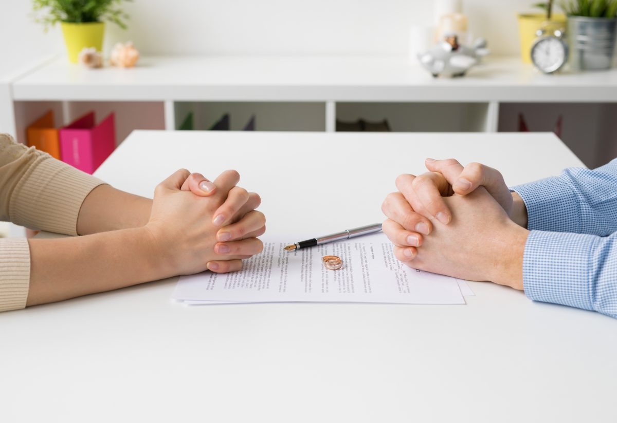 couple sitting at table with wedding rings representing how our Birmingham divorce lawyers can help you with every step of the divorce process
