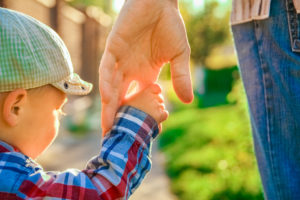 Parent holding a child's hand representing how our Clinton Township child custody attorney can help you with your case