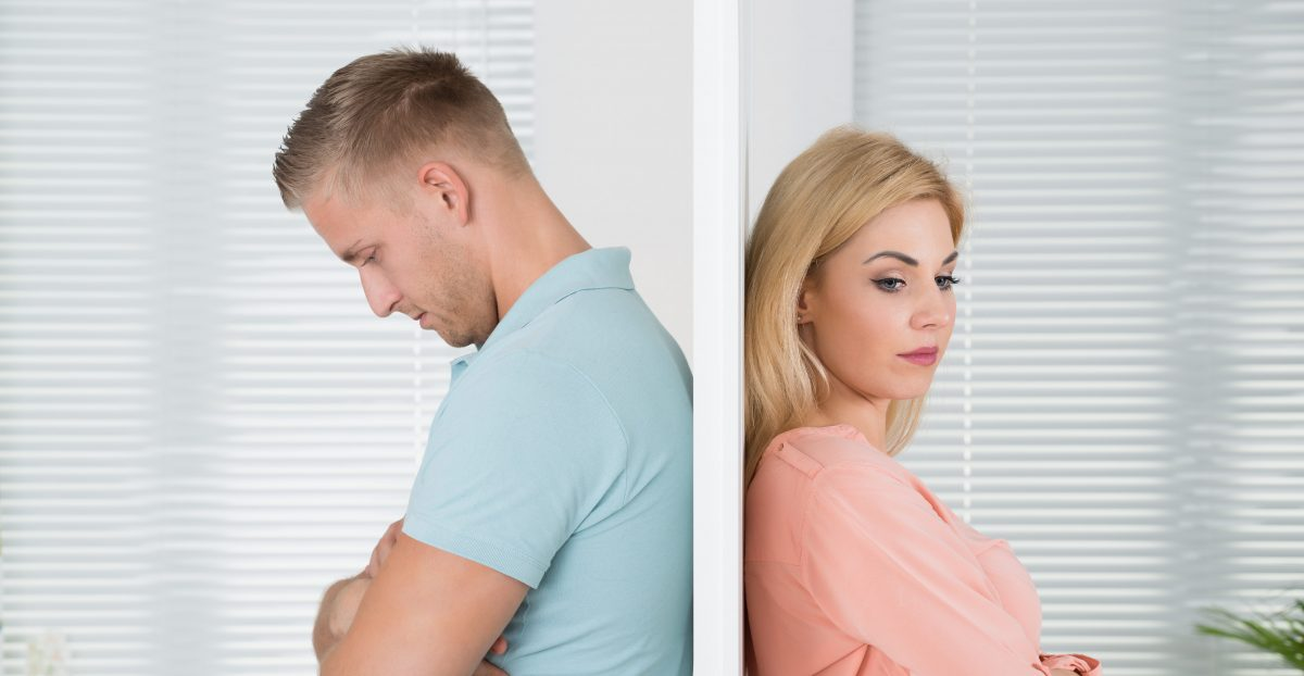 Unhappy couple standing back to back for divorce concept, meet with our experienced Royal Oak Divorce Attorneys.
