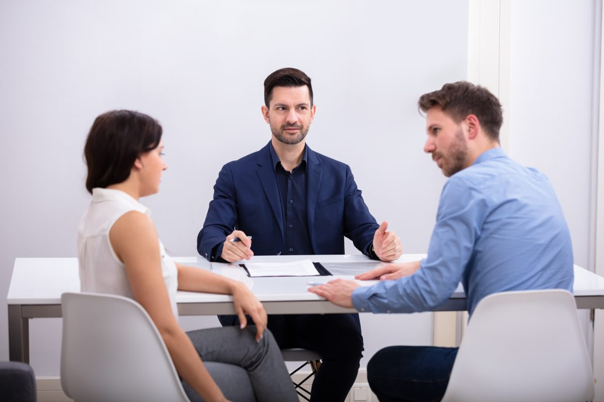 A couple having a discussion with a mediator in between them, representing how one can benefit from contacting a Clinton Township divorce lawyer.