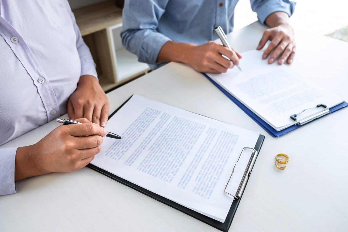 Two people sitting at a table signing divorce paper with their wedding rings on the table, representing how one can benefit from contacting a divorce lawyer from Clinton Township.