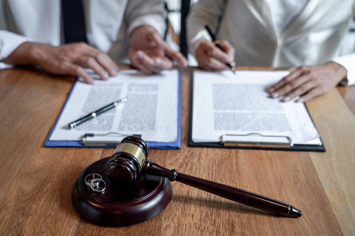Judge gavel and two rings with two people signing divorce papers, representing how one can benefit from a Sterling Heights divorce lawyer.