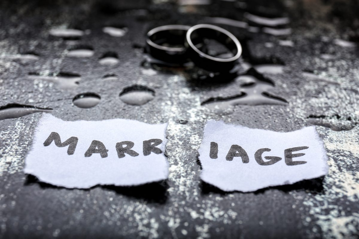 Torn paper with the word marriage and rings on wet ground, for guidance with your divorce filings meet with Michigan divorce attorney.