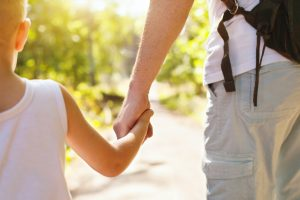 Child holding hand of parent walking outside, the child custody modification lawyer in Sterling Heights are prepared to assist with your parenting time.