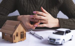 Woman removing wedding ring with house and car model on divorce paperwork, the St. Clair Shores Property Division Lawyers are experienced with dividing marital property.