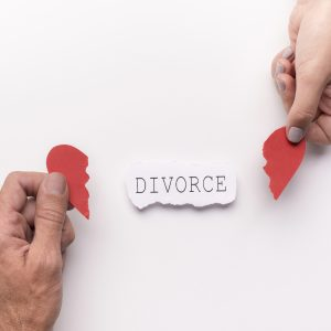 Man and woman hands each holding piece of broken red heart with divorce in center of image, the Rochester Hills Divorce Attorney will guide you through the divorce process.