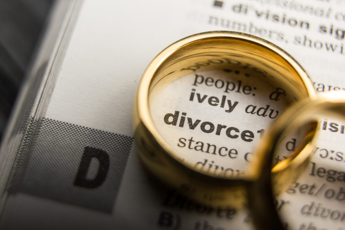 The definition of divorce in a dictionary with two wedding rings, representing how one can benefit from calling a Clinton Township divorce attorney.
