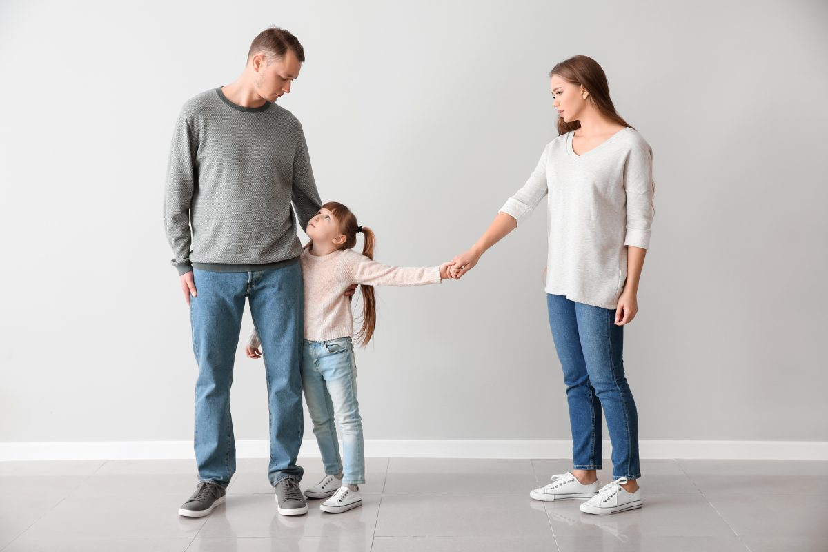 Family holds hands after getting help from a Michigan divorce attorney.