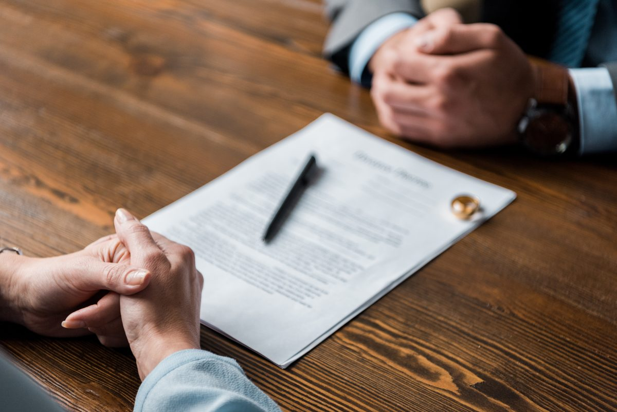 View of lawyer and client sitting at table with divorce papers and a ring, call us to speak with Divorce Lawyers Birmingham, MI.
