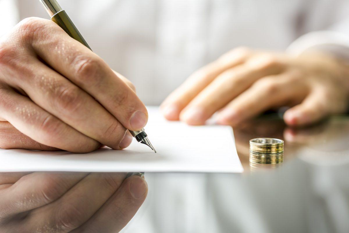 Closeup of man signing divorce paper, call a Bloomfield Hills Divorce Attorney.