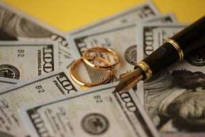 Wedding rings on hundred dollar bills with a pen, the Oakland County Complex Property Division Lawyer can assist with your divorce filing to get your rightful settlement.