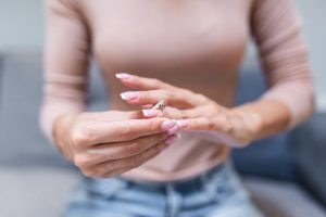Close up of woman taking off wedding ring, when deciding to divorce meet with the reliable Sterling Heights Divorce Lawyers for the best representation in your alimony issue.