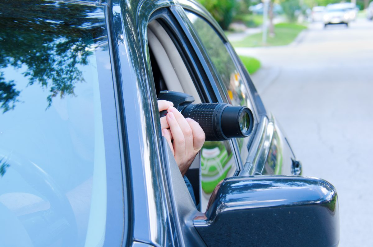 A private investigator taking pictures from his car, when beginning the divorce process it is wise to hire a good Michigan Divorce Law Firm to handle your property division.