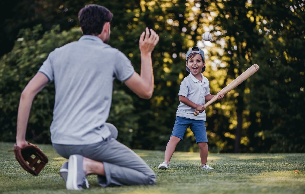 A dad throwing a baseball to son to hit with bat, when looking to change your current custody agreement speak to a Clinton Township family lawyer.