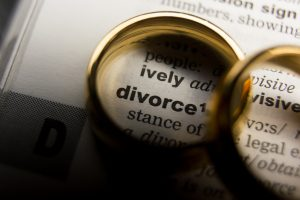 Two wedding rings surrounding the word divorce in a dictionary representing how a St. Clair Shores divorce attorney can help you navigate the divorce process.
