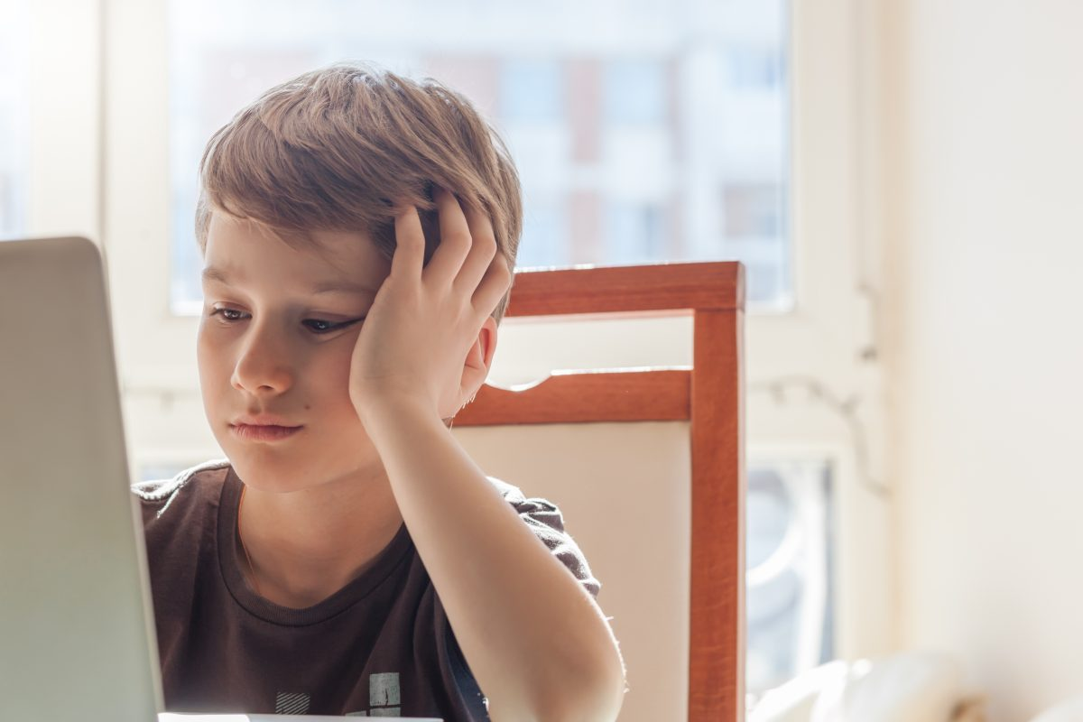 A young boy sitting working on computer for school, hen looking for a change in custody arrangement contact Child Custody Attorneys Birmingham.