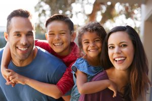 A family of four smiling, when need help with custody matters turn to Child Custody Lawyer in St. Clair Shores.